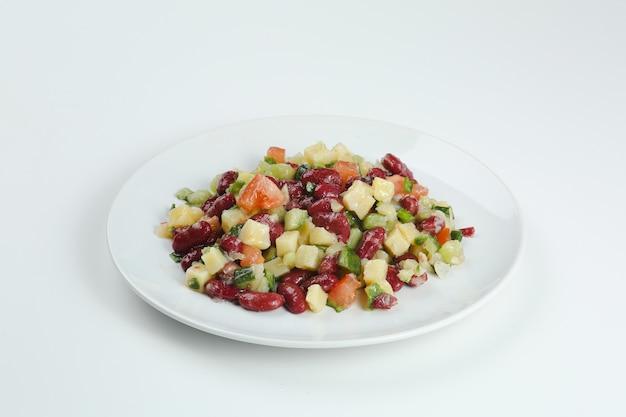 Salada com feijão, tomate, cebola, batata closeup na chapa branca. salada de feijão isolada