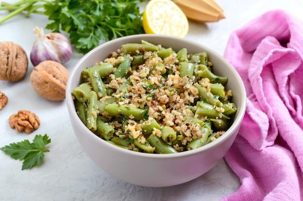 Salada com feijão verde e molho de nozes picante em uma tigela. vegetariano, menu vegan