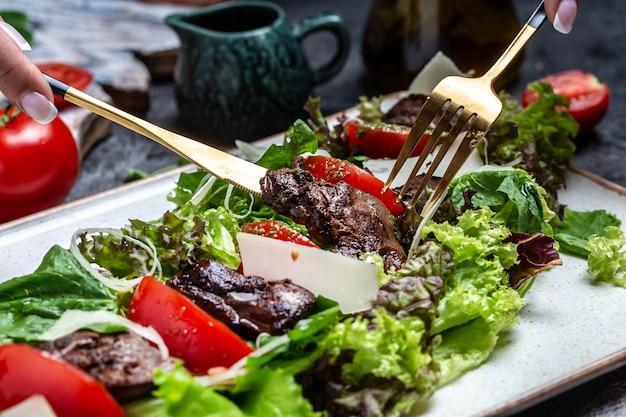 Salada com fígado de frango. salada de legumes fresca. salada de carne com fígado, salada de folhas, queijo, tomate no prato. menu de dieta. vista do topo