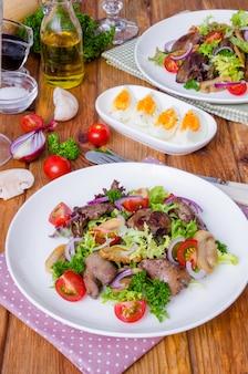 Salada com fígado de galinha, cogumelos fritos e tomate em uma madeira escura