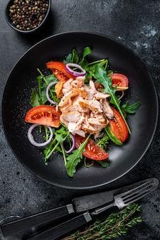 Salada com filé de salmão assado, rúcula fresca e tomate em um prato