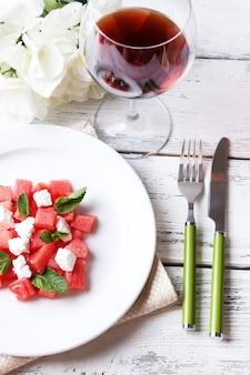 Salada com folhas de melancia, queijo feta e hortelã no prato, sobre superfície de madeira