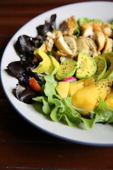 Salada com frango, abacate e manga no fundo de madeira