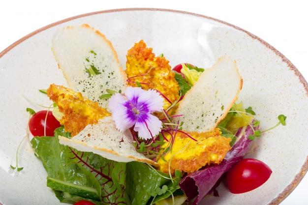Salada com frango em um prato branco sobre um fundo claro