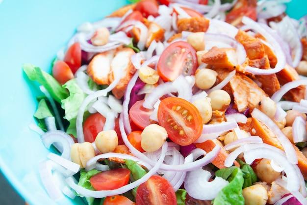 Salada com frango grelhado, tomate cereja, salada de milho, grão de bico, alface fresca e cebola.
