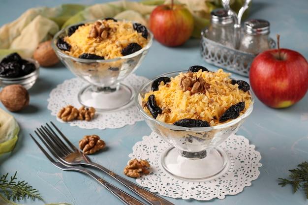 Salada com frango, queijo e maçãs, ameixas decoradas e nozes em taças de copos