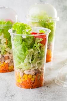 Salada com frango, tomate, cenoura e milho em tara plástica. salada de frango com legumes. isolado no fundo de mármore branco. comida caseira. menu para ir. foco seletivo. foto vertical.