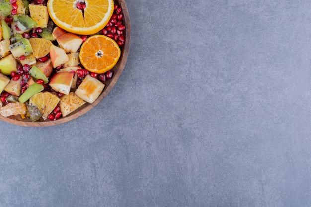 Salada com frutas da estação e temperos em superfície de concreto
