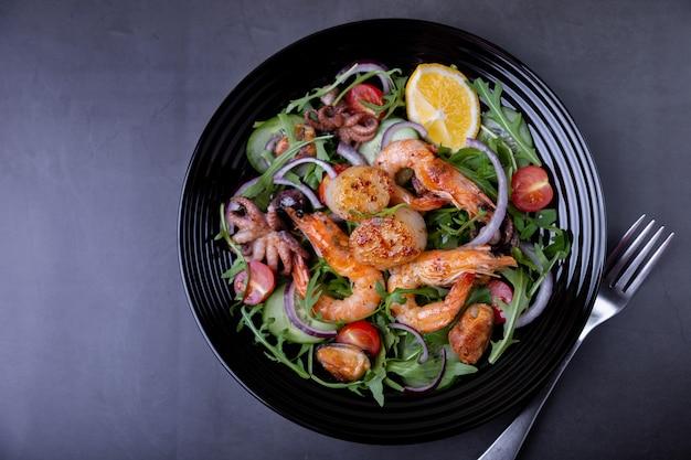 Salada com frutos do mar, rúcula, tomate, pepino, cebola roxa e limão em uma placa preta. fundo preto, close-up.