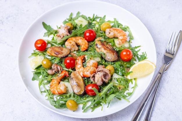Salada com frutos do mar, rúcula, tomate, pepino e azeitonas em um prato branco