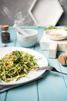 Salada com garfo na mesa de madeira e fundo desfocado