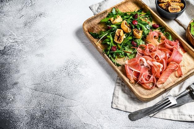 Salada com jamon serrano, presunto, rúcula e figo. antipasto. fundo cinza, vista superior, espaço para texto