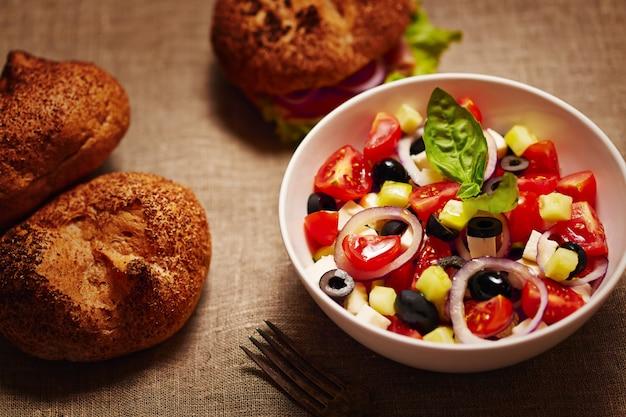 Salada com legumes frescos e hambúrguer e pãezinhos