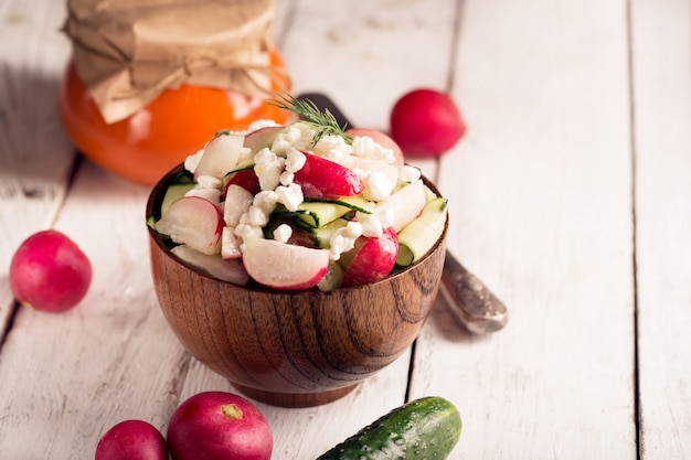 Salada com legumes frescos e queijo cottage. orientação horizontal. mesa de madeira