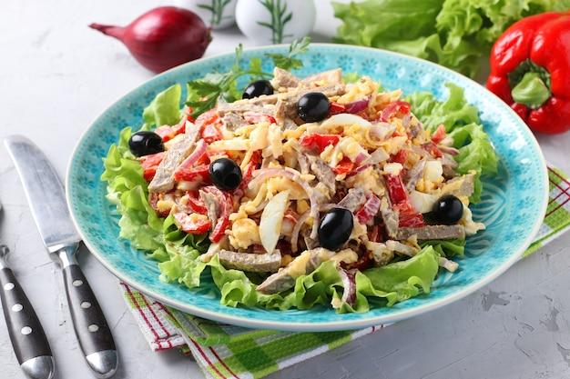 Salada com língua, pimentão, ovos, alface, queijo e azeitonas pretas em prato azul sobre superfície cinza