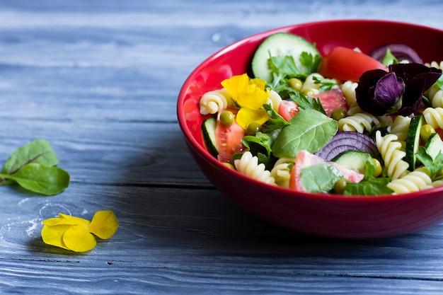 Salada com macarrão e legumes frescos. em um prato vermelho.