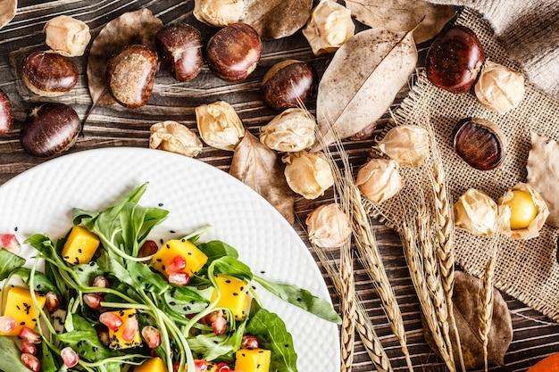 Salada com manga, abóbora assada, rúcula, sementes de romã deitado no prato branco.