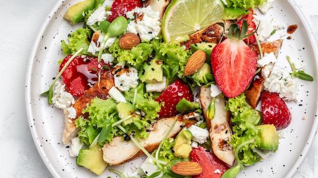 Salada com morango, frango, abacate, queijo feta, alface e nozes em vinagre balsâmico. alimentação limpa para perda de peso. fundo de receita de comida. fechar-se.