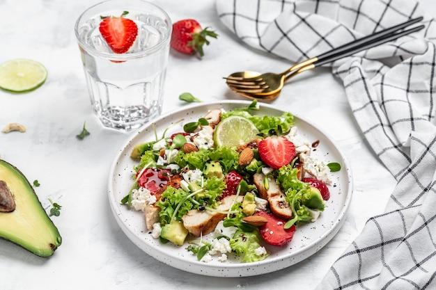 Salada com morango, frango, abacate, queijo feta, alface e nozes em vinagre balsâmico. conceito de deliciosa comida equilibrada. vista do topo.