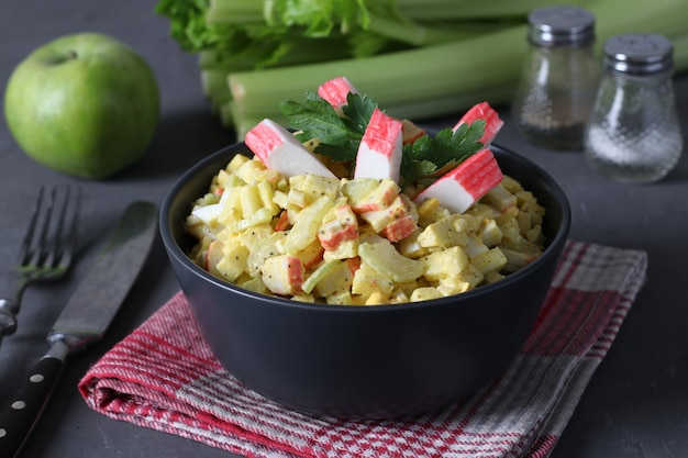 Salada com palitos de caranguejo, aipo, maçã e ovos de codorna em uma tigela escura sobre fundo cinza. alimentação saudável.
