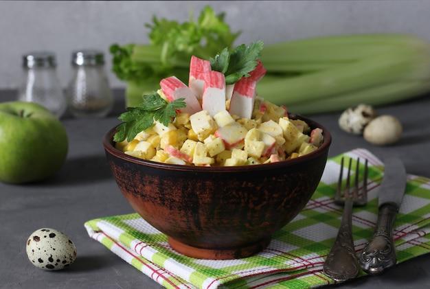 Salada com palitos de caranguejo, aipo, maçã e ovos de codorna em uma tigela escura sobre um fundo cinza. alimentação saudável.