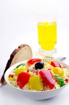 Salada com palitos de caranguejo, arroz, vegetais e um copo de suco