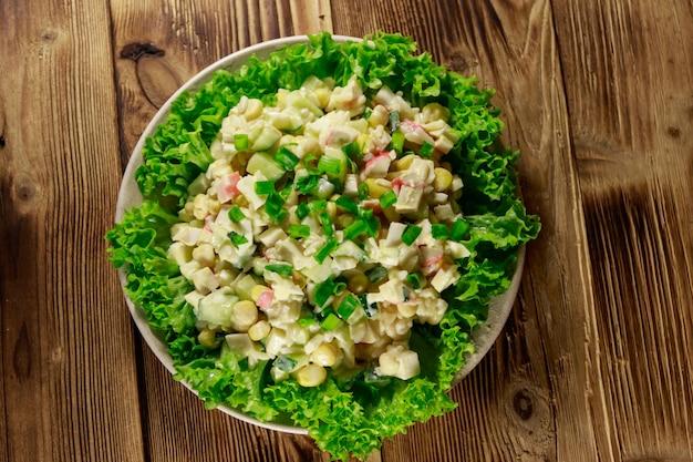 Salada com palitos de caranguejo, milho doce, pepino, ovos, arroz e maionese na mesa de madeira. vista do topo