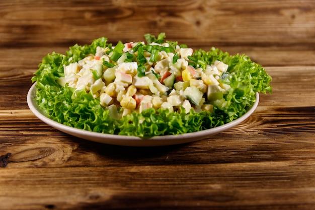 Salada com palitos de caranguejo, milho doce, pepino, ovos, arroz e maionese na mesa de madeira