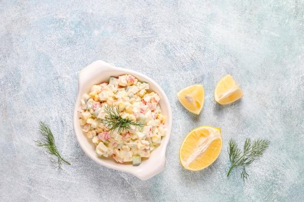 Salada com palitos de caranguejo, ovos, milho e pepino.