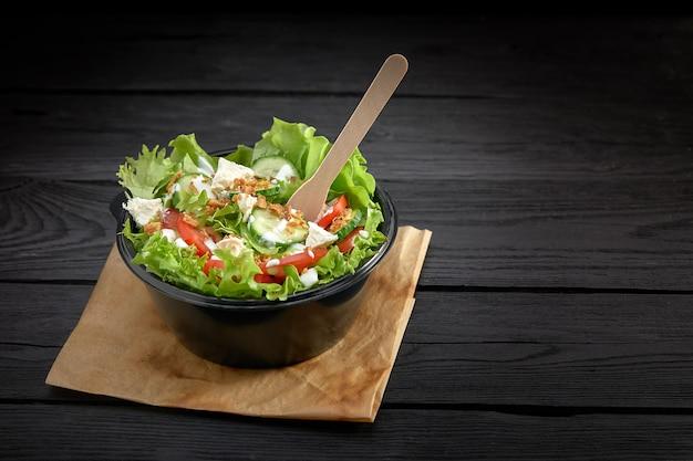 Salada com peixe vermelho ou atum e lettucce em uma tigela de plástico. fast-food saudável.