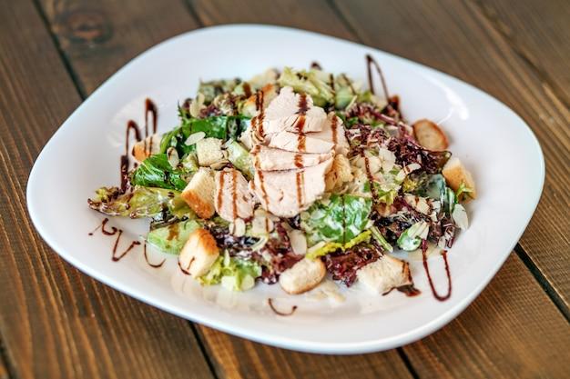 Salada com pepino e galinha e alface em uma placa branca.