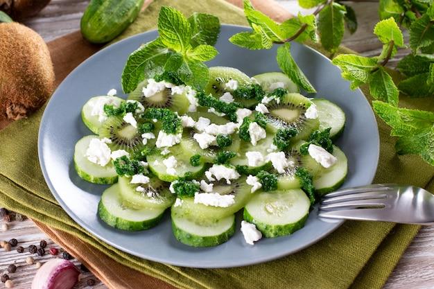 Salada com pepino, kiwi, hortelã e queijo cottage em um prato. alimentação saudável