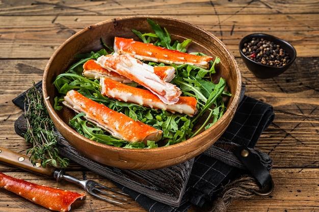 Salada com pernas de king crab em uma placa de madeira. fundo de madeira. vista do topo.