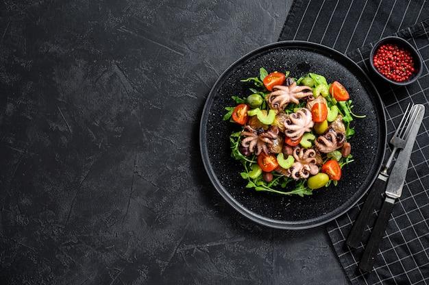 Salada com polvo grelhado, batatas, rúcula, tomate e azeitonas. fundo preto. vista do topo. espaço para texto