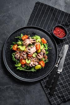 Salada com polvo grelhado, batatas, rúcula, tomate e azeitonas. fundo preto. vista do topo
