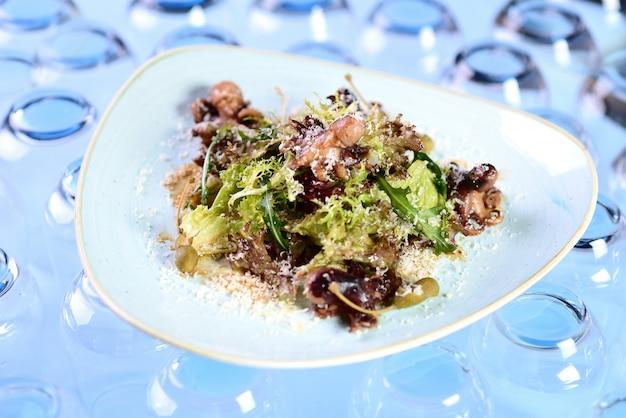 Salada com polvo, rúcula, alcaparras e queijo ralado
