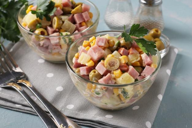 Salada com presunto, azeitonas, milho e abacaxi em tigelas de salada transparentes sobre uma superfície azul clara, closeup
