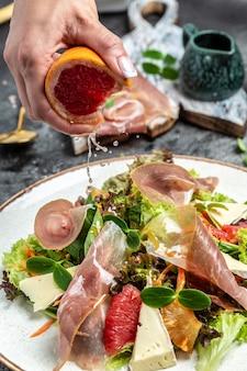 Salada com presunto, presunto, jamon e toranja, mistura para salada, toranja, tomate cereja, queijo parmesão. lanches frios. congele o movimento de respingos de gotas de suco de toranja,