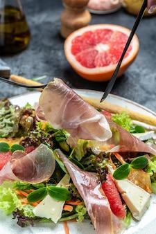 Salada com presunto, queijo brie camembert e toranja, mistura para salada. gorduras saudáveis, alimentação limpa para perda de peso.