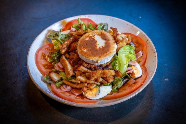 Salada com presunto, queijo e frango em um fundo preto, em um prato branco