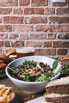 Salada com queijo de cabra, hambúrgueres caseiros com batatas fritas, bebida e bolo na mesa de madeira. imagem vertical isolada.