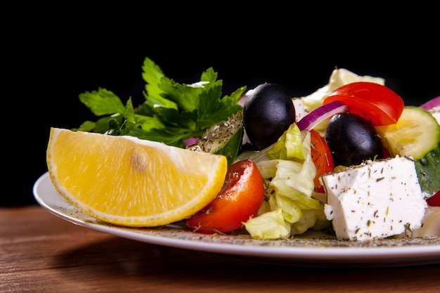 Salada com queijo de feta, azeitonas, alface, tomates, pepino, limão no fundo preto.