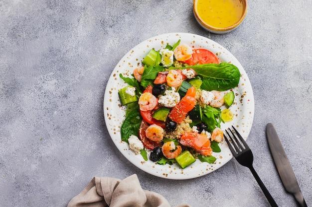Salada com quinoa, alface, rúcula, pepino, azeitonas pretas, tomate, queijo cottage, salmão, camarão e molho de manga, searved na parede cinza com guardanapo de linho. comer limpo para imunidade