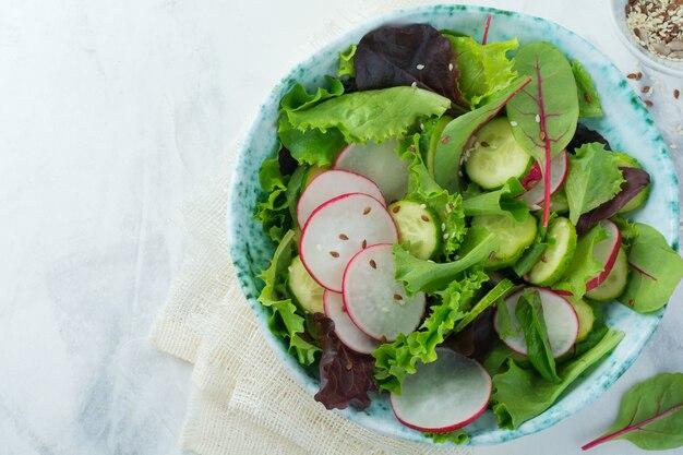 Salada com rabanetes frescos, rúcula, beterraba, acelga, sementes de girassol, sementes de linho e gergelim em um fundo claro