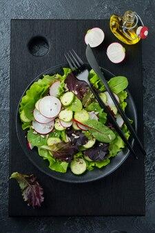 Salada com rabanetes frescos, rúcula, beterraba, acelga, sementes de girassol, sementes de linho e gergelim em um fundo preto