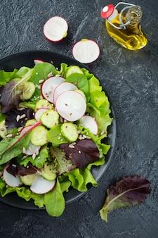 Salada com rabanetes frescos, rúcula, beterraba, acelga, sementes de girassol, sementes de linho e gergelim em uma superfície preta