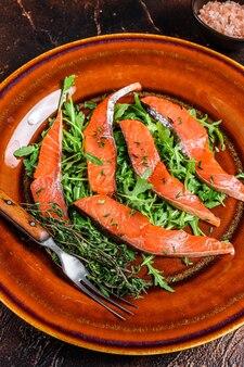 Salada com rúcula e fatias de filé de salmão defumado na mesa de madeira. vista do topo.