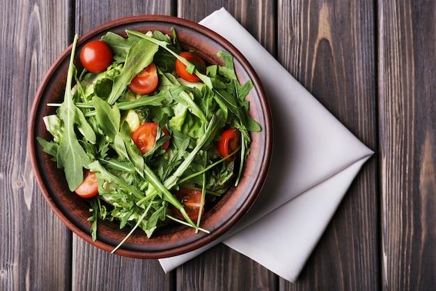Salada com rúcula e tomate cereja na mesa de madeira