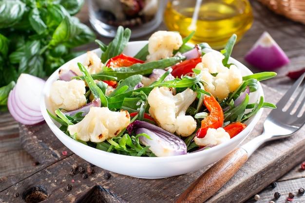 Salada com rúcula, legumes assados (couve-flor, pimentão vermelho e cebola) e sementes. comida saudável.