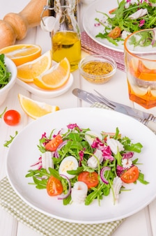 Salada com rúcula, lula, tomate cereja, cebola e codorna ovos sobre fundo branco de madeira.
